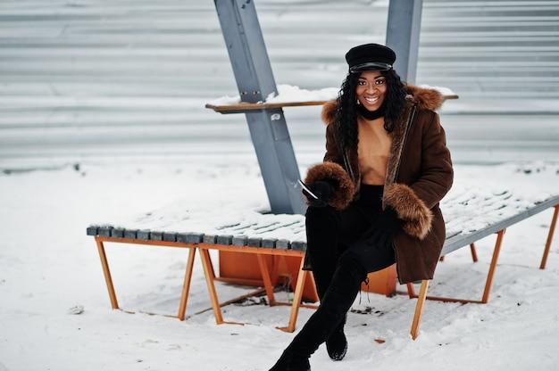 Афро-американских женщина в полушубке и кепке позирует в зимний день на снежном фоне, сидя на скамейке с телефоном под рукой. Premium Фотографии