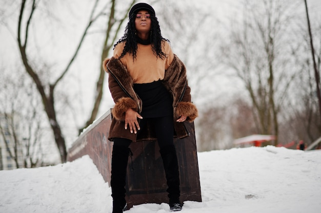 Афро-американская женщина в дубленке и кепке представляла в зимний день на снежном фоне. Premium Фотографии