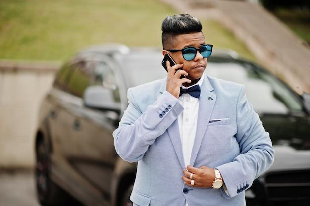 Стильный арабский мужчина в куртке, галстуке-бабочке и солнцезащитных очках на фоне черного внедорожника. арабские богатые говорят по мобильному телефону. Premium Фотографии