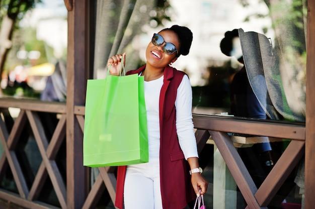 屋外歩行色の買い物袋を持つカジュアルなアフリカ系アメリカ人の女の子。スタイリッシュな黒人女性のショッピング。 Premium写真
