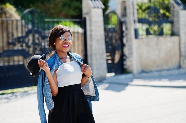 メガネ帽子、ジーンズジャケット、屋外でポーズの黒のスカートでスタイリッシュなアフリカ系アメリカ人モデル。 Premium写真