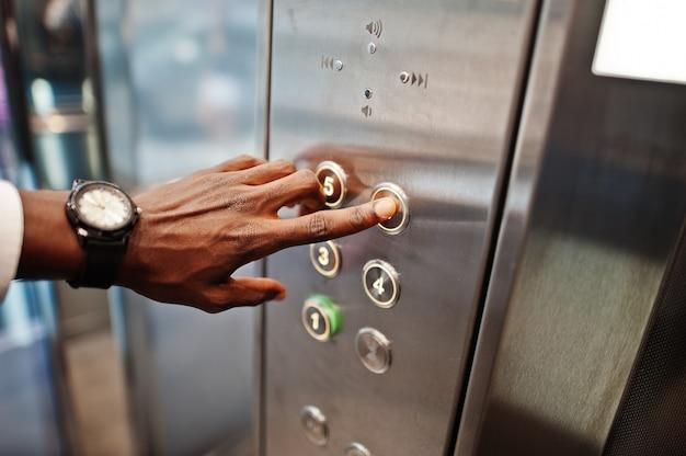 Крупным планом фото мужской руки с часами на элеватор или современный лифт, нажав кнопку Premium Фотографии