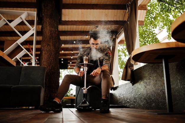 メガネとストリートバーで水ギセル喫煙ミリタリージャケットのスタイリッシュなひげ男 Premium写真
