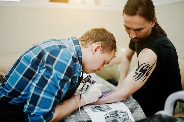 タトゥーマスターがロッカーマンのタトゥーを作る Premium写真