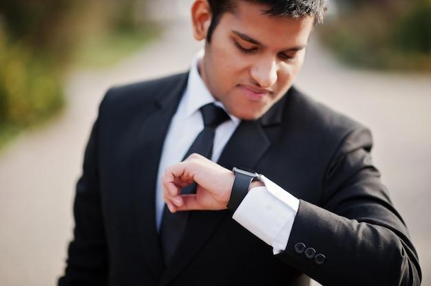 Элегантный южно-азиатский бизнесмен в костюме смотря его умные вахты в наличии. Premium Фотографии