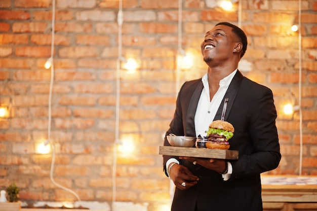 Респектабельный довольный молодой человек в черном костюме держит поднос с двойным бургером у кирпичной стены ресторана с огнями Premium Фотографии