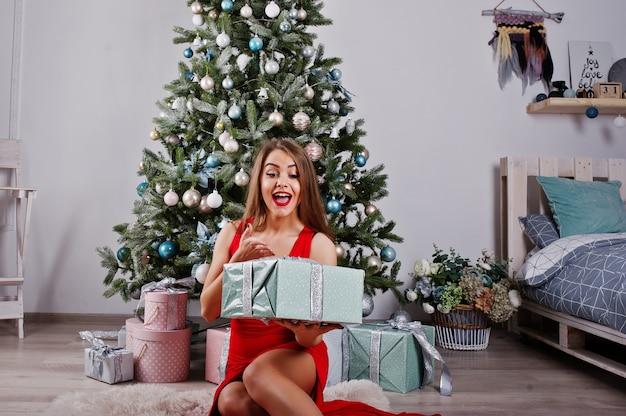 Модная шикарная женщина в красном длинном вечернем платье позировала против новогодней елки с подарками. тема рождественских каникул. Premium Фотографии