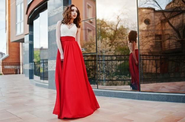 赤いイブニングドレスでファッショナブルな女の子の肖像画は、モダンな建物の背景ミラーウィンドウを提起 Premium写真