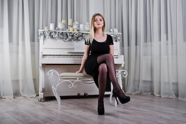 白い部屋でクリスマスキャンドルの装飾が付いているピアノの近くでポーズをとって黒のドレスでブロンドの女の子。 Premium写真