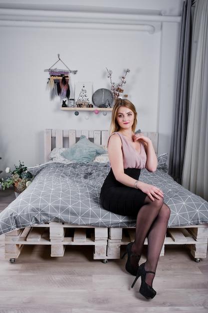 Белокурая девушка в платье представила на кровати около рождественской елки с украшением рождественских подарков в белой комнате. Premium Фотографии