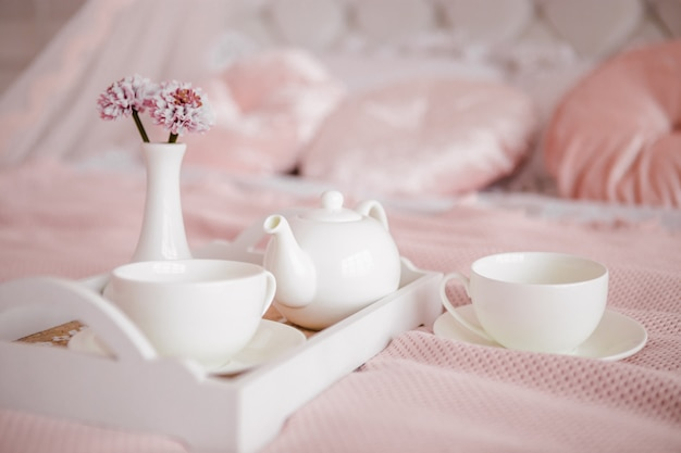 花と白いカップを備えたベッドでの朝食。 Premium写真