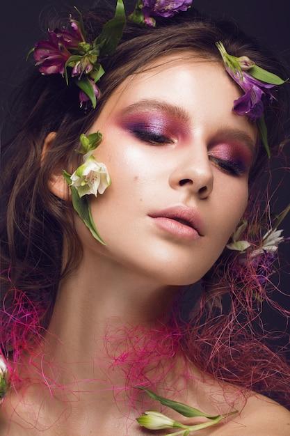 Красивая девушка с художественным макияжем и цветами Premium Фотографии