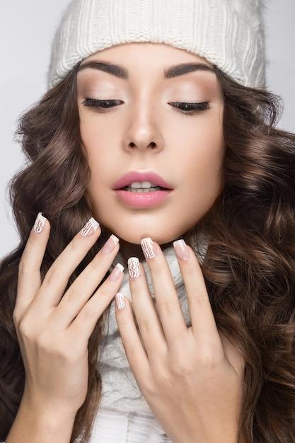 Красивая женщина с нежным макияжем, дизайнерским маникюром и улыбкой в белой вязаной шапке Premium Фотографии