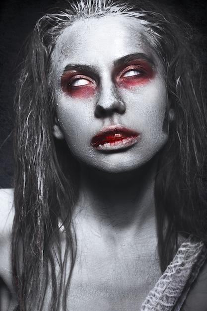 ゾンビの形の女の子、彼の唇に血でハロウィーンの死体 Premium写真