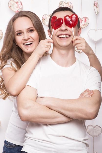 Молодая, красивая женщина и влюбленный мужчина на день святого валентина с конфетами Premium Фотографии