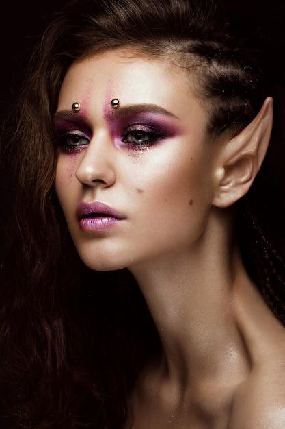 創造的な髪型三つ編み、アートメイク、エルフの耳を持つブルネットの少女。美容顔。 Premium写真