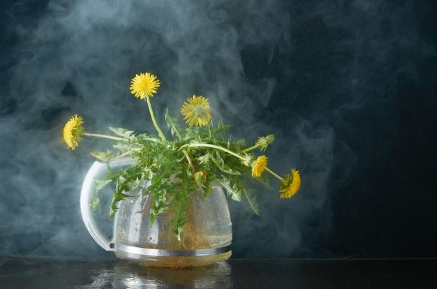 Одуванчик с корнями и листьями в стеклянном чайнике на темном дыму Premium Фотографии