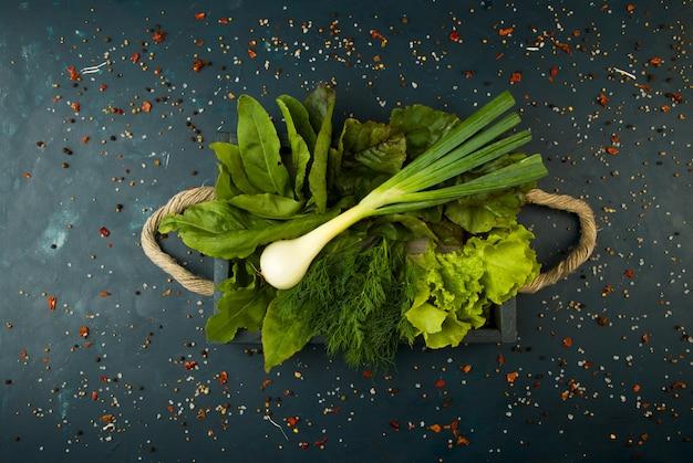 ストーン・ア・ダークの箱に入っている野菜。ヤンググリーンオニオンガーリックズッキーニブライトスパイスは、暗い質感のロープハンドル付きの木製の箱に入っています。 Premium写真