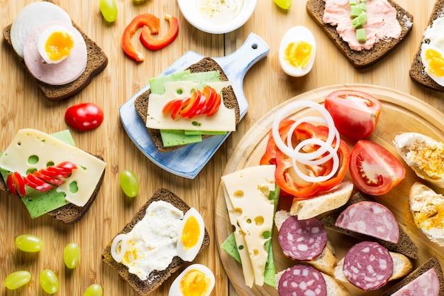 Стол для завтрака с бутербродами с сыром, колбасой, овощами, яйцами вкрутую и фруктами Premium Фотографии