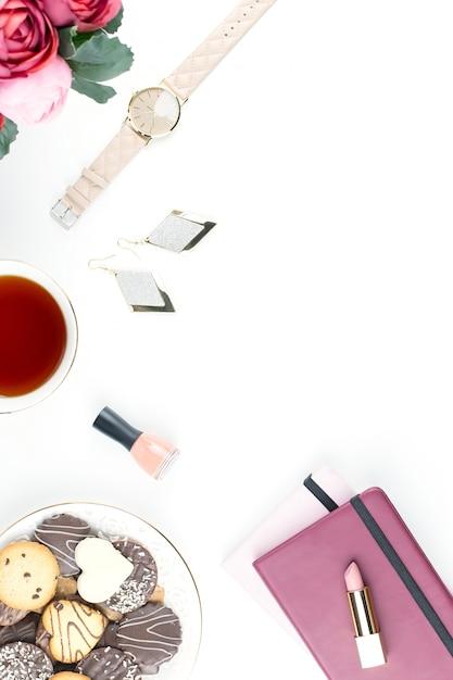 フラットレイアウトのホームオフィスデスク。日記、花、お菓子、ファッションアクセサリーを備えたフェミニンなワークスペース。ファッションのブロガーのコンセプト。 Premium写真