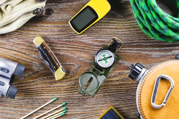 Туризм или путешествия оборудование с сапоги, компас, бинокль, спички на деревянных фоне. концепция активного образа жизни Premium Фотографии