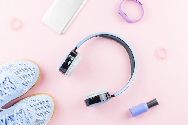 Женщина кроссовки, наушники, фитнес-трекер и смартфон на пастельных розовом фоне. концепция спортивной моды. плоская планировка Premium Фотографии