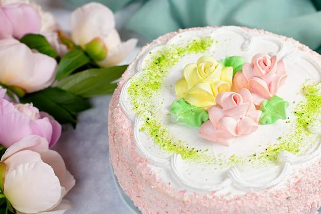 Красивый вкусный торт украшенный цветами в пастельных тонах на деревянный стол с пионами, вид сверху Premium Фотографии