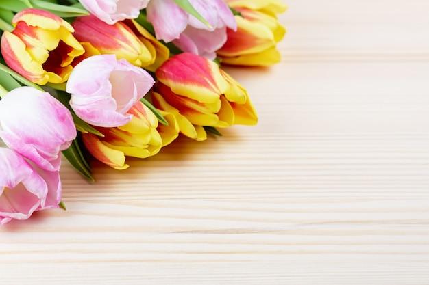 Красные и розовые тюльпаны на деревянном столе крупным планом, копией пространства Premium Фотографии