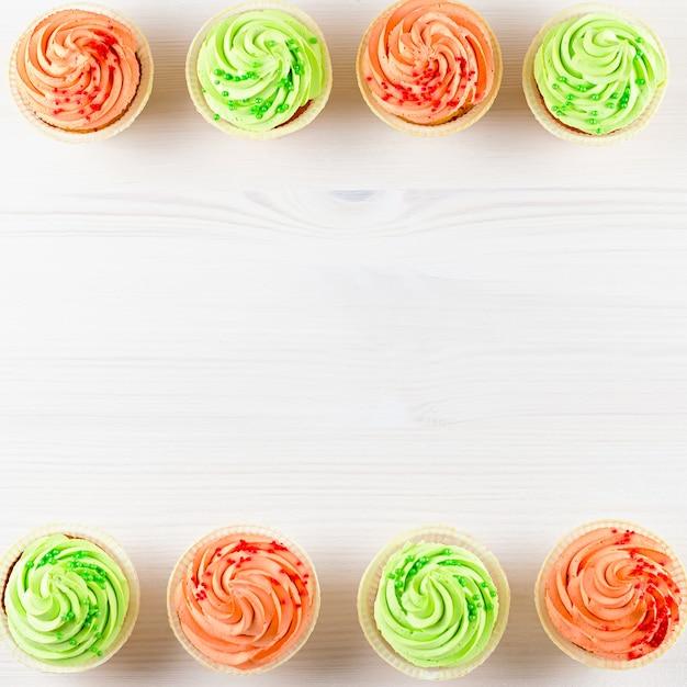 Вкусные красочные кексы крупным планом на белом деревянном столе, вид сверху Premium Фотографии