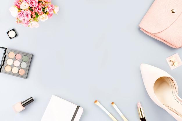 フラットのファッションブロガーワークスペースには、ポンプ、化粧品、財布、プランナーの本、花が横たわっていた。 Premium写真
