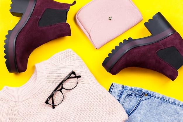 Осенняя женская одежда - розовый свитер, синие джинсы, кожаная сумка, толстые ботильоны, аксессуары Premium Фотографии