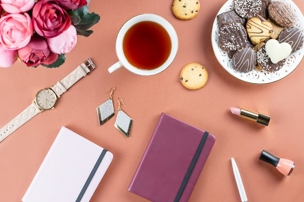 フラットレイアウトのホームオフィスデスク。日記、花、お菓子、ファッションアクセサリーのあるフェミニンなワークスペース。ファッションのブロガーのコンセプトです。 Premium写真