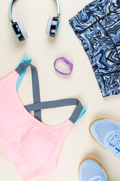 中立的なテーブルの女性スポーツ服、スニーカー、ヘッドフォン、フィットネストラッカー。スポーツファッションのコンセプトです。フラットレイ Premium写真