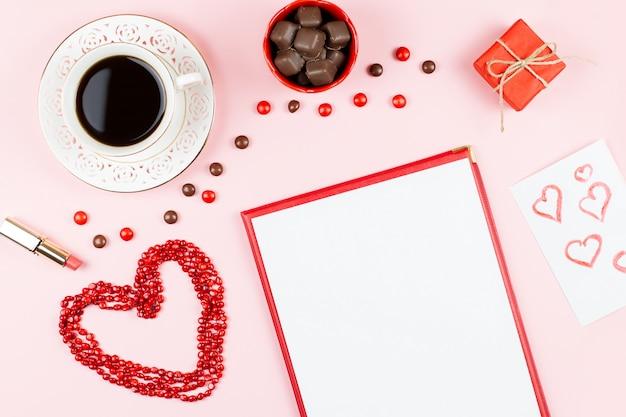 Шоколадные конфеты, горячий напиток, губная помада, лист бумаги, подарочная коробка. женственный фон в красных и белых тонах. Premium Фотографии