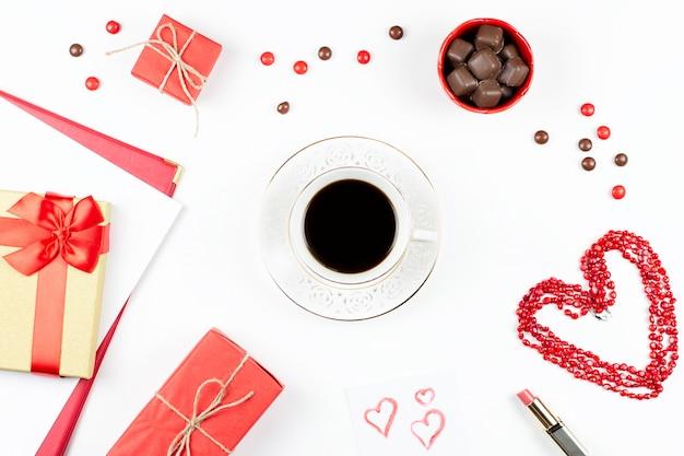 Кофейная чашка, конфеты, помада, форма сердца и подарочная коробка на белой поверхности Premium Фотографии