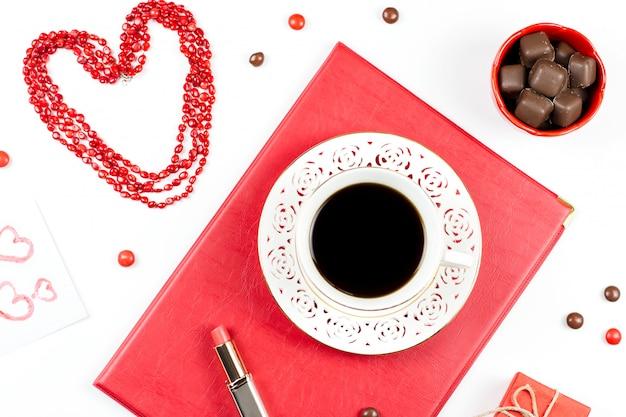 Кофейная чашка, конфеты, губная помада, форма сердца и подарочная коробка на белой поверхности. женский день концепция плоской планировки. Premium Фотографии
