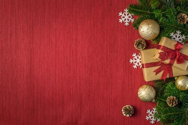 ギフト、ゴールデンボール、松ぼっくり、モミの枝、赤の背景に雪の結晶クリスマス組成 Premium写真