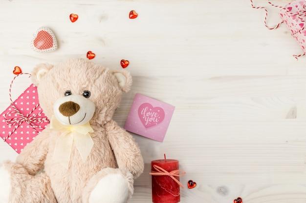 День святого валентина сцена с мишкой, подарочные коробки, открытки и сердца на светлом фоне деревянные. Premium Фотографии