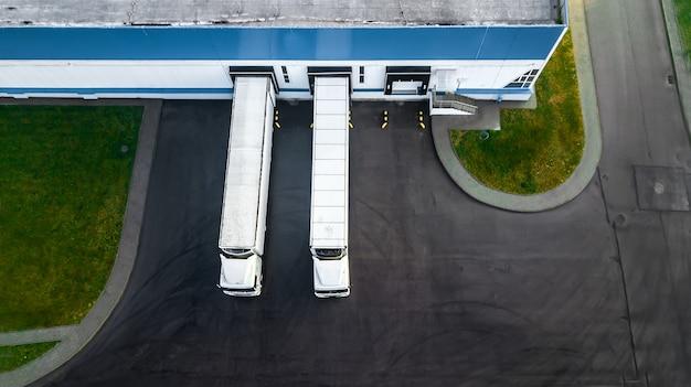 Грузовые автомобили загружаются в современный логистический центр. с высоты птичьего полета. Premium Фотографии