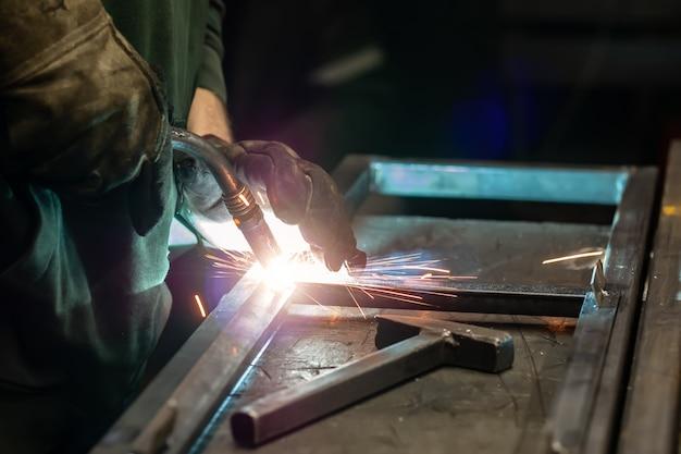 Сварщик готовит раму. сварщик готовит металл. сварщик готовит металлические конструкции. сварочные работы искры, расплавленный металл Premium Фотографии