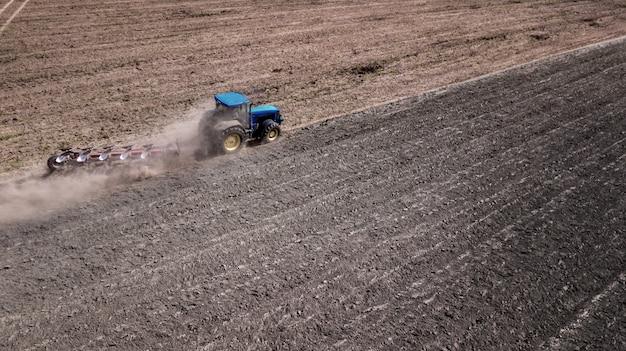 トラクター耕すフィールドトップビュー、ドローンと空中写真 Premium写真