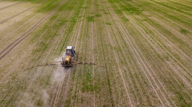 Аэрофотоснимок сельскохозяйственного трактора вспашки и опрыскивания на поле Premium Фотографии