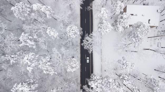 冬の森、通り過ぎるトラック、モーションブラーの雪に覆われた道路の空撮 Premium写真