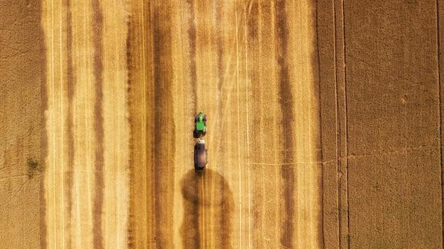 大麦畑で作業するコンバインの空撮 Premium写真