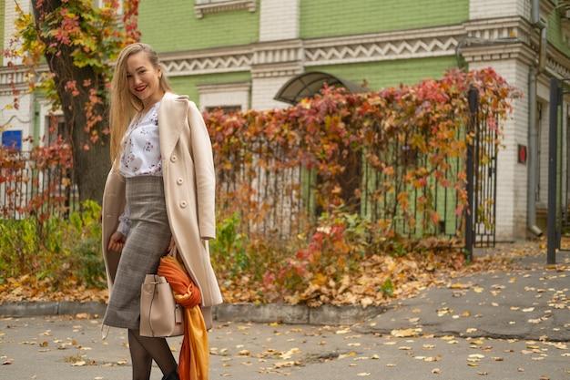 スタイリッシュな古典的な服を着ている若い美しい女性のストリート写真。下へ見ているモデル。女性のファッションのコンセプト。 Premium写真