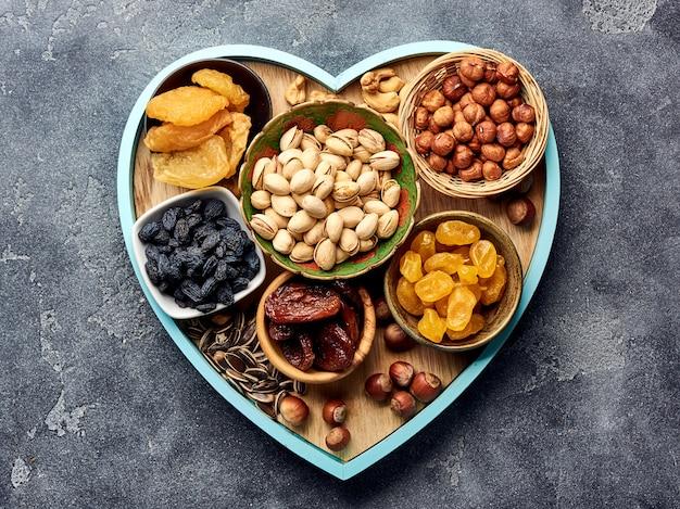Смешайте сухофрукты и орехи на серой поверхности. вид сверху суперпродуктов. Premium Фотографии