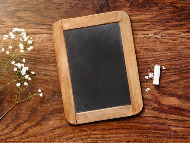 チョークボードと木製のテーブルにチョーク。 Premium写真