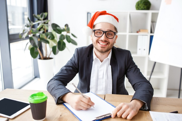Молодой веселый бизнесмен в офисе. Premium Фотографии