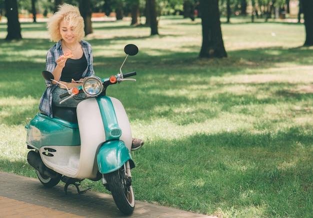 Девочка ест на мото скутере или мопеде. девочка ест на мото скутере или мопеде. счастливая молодая женщина, держащая горячую пиццу в коробке. студентка не успевает, он собирается кушать на ходу Premium Фотографии