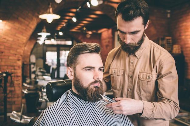Два серьезных парня в парикмахерской. один из них - клиент, который сидит в кресле, пока парикмахер делает немного магии, подрезая часть бороды. Premium Фотографии